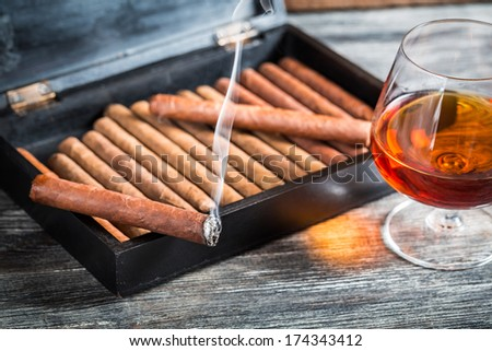 Burning cigar on humidor and cognac - stock photo