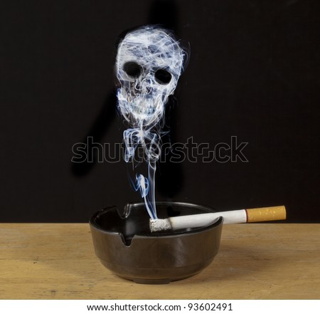 Burning cigarette in an ashtray with a skull formed of smoke , a warning of the hazards of smoking - stock photo