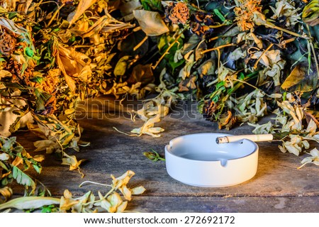 Burning cigarette in ashtray on grunge wood table with yellow sun light - stock photo