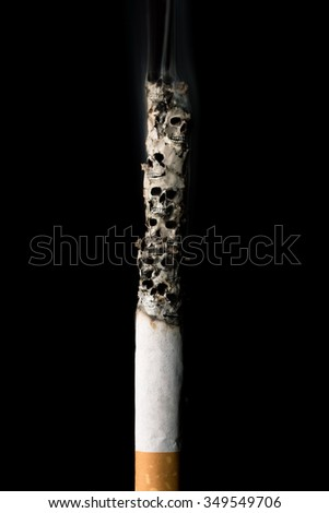 burning cigarette with ash and skulls - stock photo