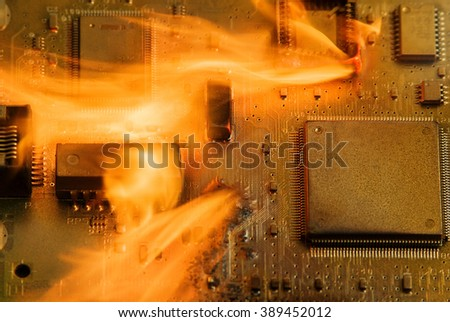 Burning circuit board with electronic components. Computer, technology and fire protection concept.  - stock photo