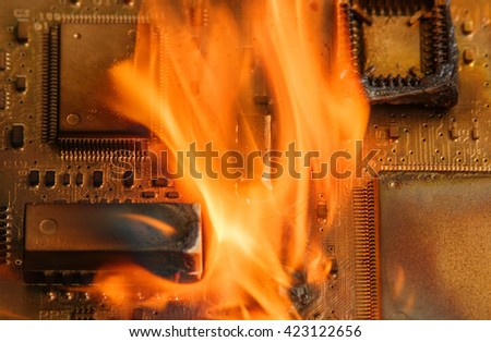 Burning circuit board with electronic components. Computer, technology, repair and fire protection concept.  - stock photo