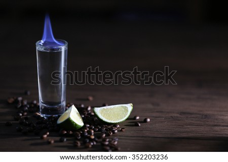 Burning cocktail with lime and coffee beans on wooden background - stock photo