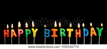 Burning colorful candles on black background, words happy birthday