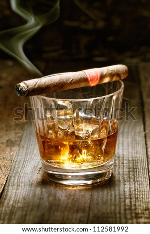 Burning Cuban cigar resting on glass of whisky on ice on an old wooden surface symbolic of masculinity
