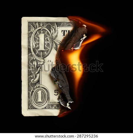 Burning dollar on black background - stock photo