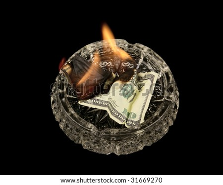 Burning dollars in ashtray isolated on black background - stock photo