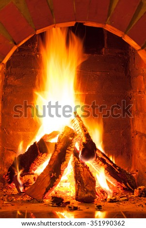 Burning fire in the brick fireplace, close up - stock photo
