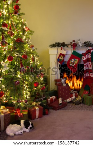 Burning fireplace and a dog sleeping under the christmas tree - stock photo