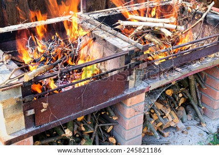 Burning firewood in self made brick and metal brazier or grill - stock photo