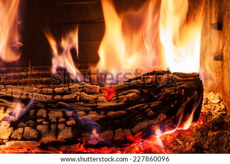 Burning firewood in the fireplace close up - stock photo