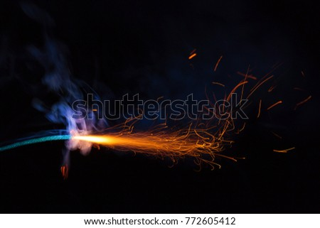 Burning fuse with sparks and blue smoke on black background