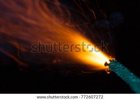 Burning fuse with sparks on black background