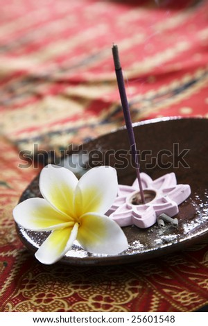 burning incense placed in the plate on batik background - stock photo