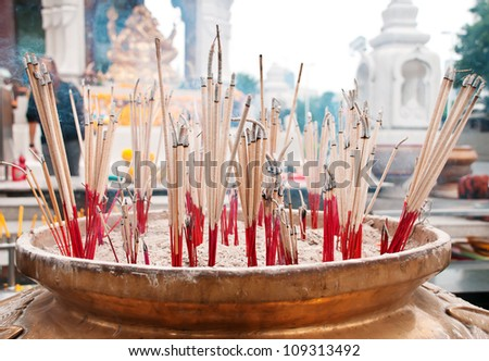 burning incense sticks in brass Incense bowl at buddhist shrine - stock photo
