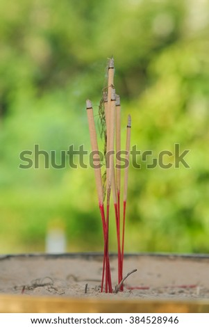 Burning incense sticks in Buddhist temple of Thailand.  - stock photo