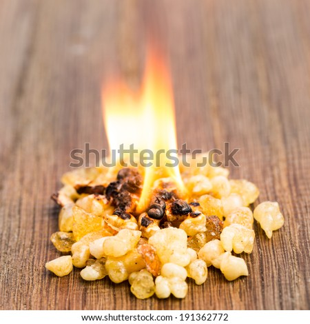 Burning incense with flame on wood - stock photo