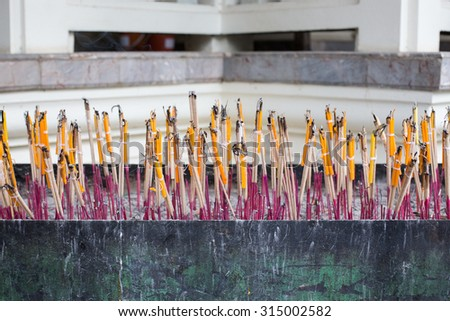 Burning joss stick and candle in joss stick pot - stock photo