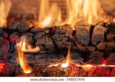 Burning log of wood in a fireplace close-up - stock photo