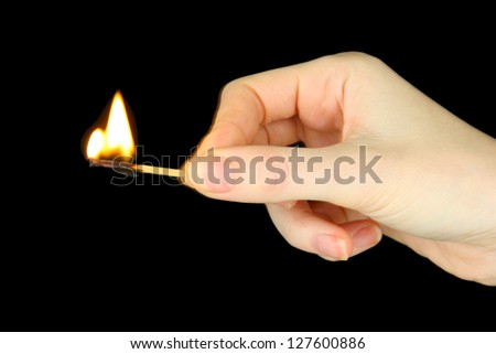 Burning match in female hand, isolated on black - stock photo