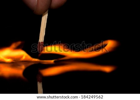 Burning match just after ignition with reflection in glass - stock photo