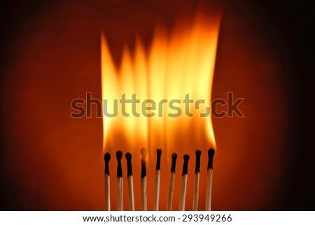Burning matches on dark color background - stock photo