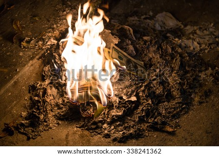 Burning money - 100 american dollar banknotes in flames - stock photo