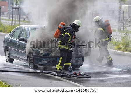 Burning motor vehicle been put out by firemen in protective clothing