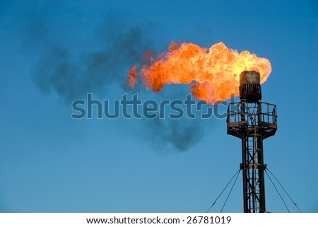 Burning oil flare on a blue sky - stock photo