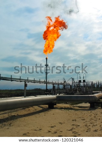 Burning oil gas flare over the blue sky - stock photo