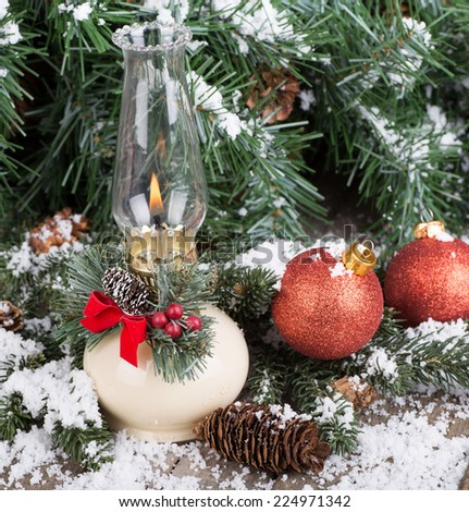 Burning oil lamp and Christmas balls with snowy evergreen tree - stock photo