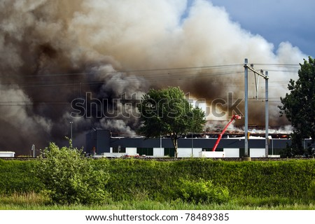 Burning recycling factory with heavy smoke and fire fighters trying to control the fire - stock photo