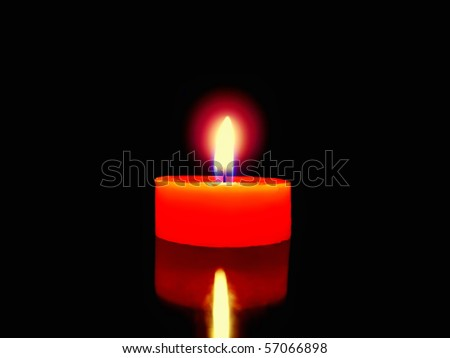 Burning red candle in the dark