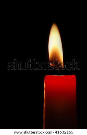 Burning red candle on black background - stock photo