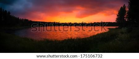 Burning sky sunset panorama on the lake in Kuusamo, Finland. - stock photo