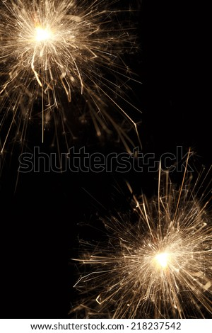 Burning sparklers in front of a black background - stock photo