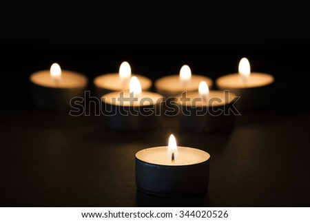 Burning tealights in darkness - stock photo