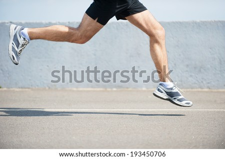 Burning the miles away.  Side view close-up image of man running outdoors