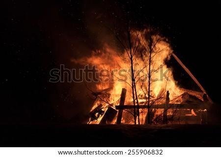 Burning wood house. Ruins. Dark night. - stock photo