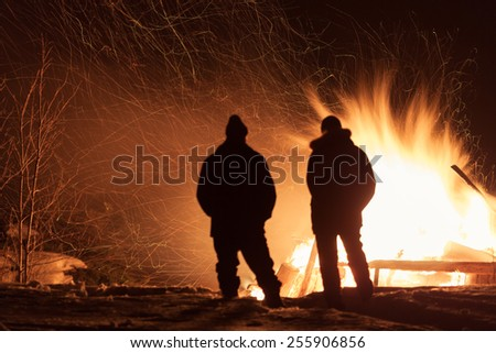 Burning wood house. Ruins. Dark night. Two men silhouettes.