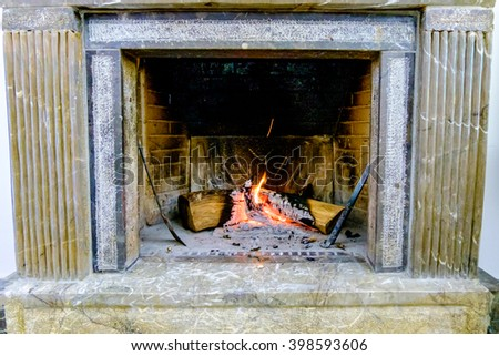 burning wood in stonework fireplace - stock photo