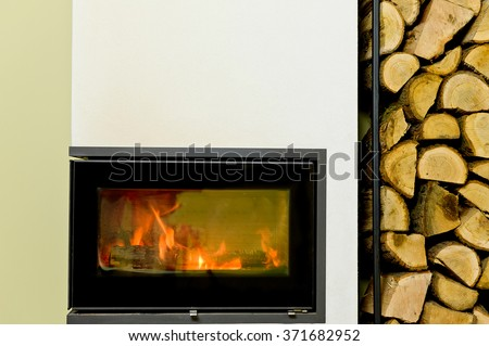 burning wood in wood stove. Wood stand with wood