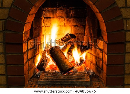 burning wooden logs in fire-box of fireplace in country cottage - stock photo