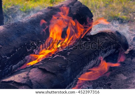 Burning wooden logs with big fire flames as abstract background. Flame burning texture, blazing fire, flame, burning logs, firewood, coal, ash, smoke, fire. Macro texture flame from the burning logs - stock photo