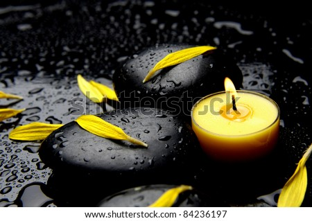 Burning yellow candle with yellow flower petals in water drops - stock photo