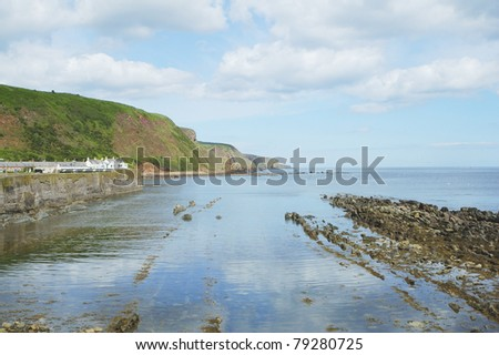 Burnmouth harbour wall and cliffs beyond with seascape - stock photo