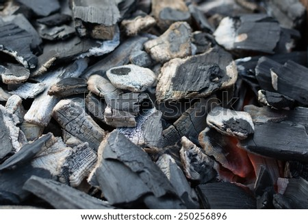 Burnt charcoal and ash with a small glow. - stock photo