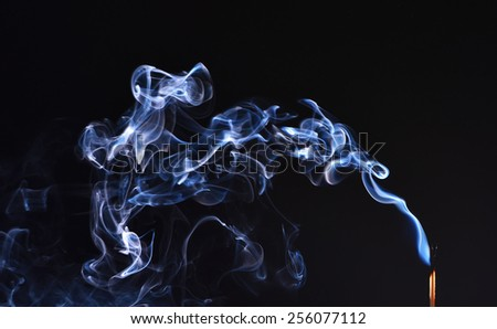 Burnt match in a smoke on a black background. cyan smoke comes out from an extincted match - stock photo