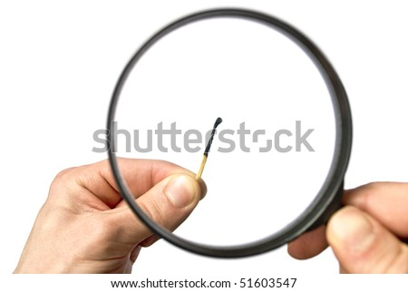 Burnt match under the magnifier, whis is held by male hands. Isolated on white - stock photo