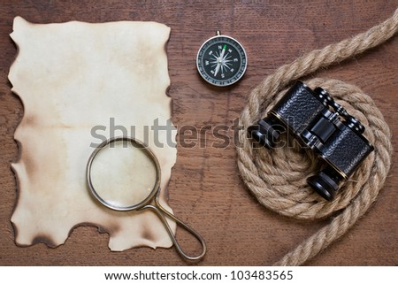 Burnt paper, compass, magnifying glass, binoculars, rope on the old wooden background